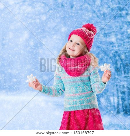 Little girl in blue knitted sweater and pink hat catching snowflakes in winter park. Kids play outdoor in snowy forest. Children catch snow flakes. Toddler kid playing outside in snow storm.