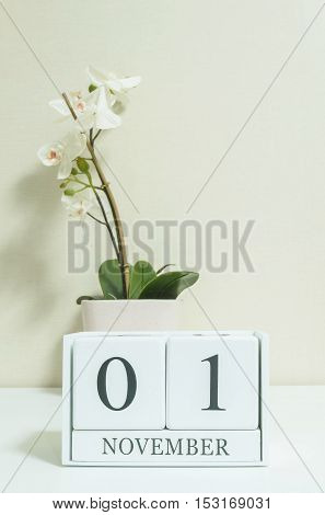 Closeup white wooden calendar with black 1 november word with white orchid flower on white wood desk and cream color wallpaper in room textured background selective focus at the calendar