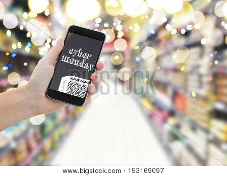 hand holding mobile smart phone with mobile shop on supermarket blur background and shopping bags - cyber monday e-commerce concept