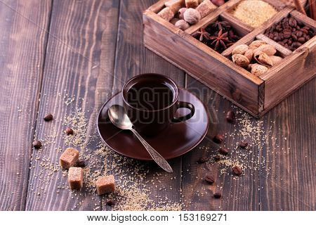 Cup of black coffee, roasted coffee beans and spices in a wooden printers box. Coffee beans, anise stars, brown sugar, walnut, hazelnut and nutmeg.