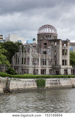 Hiroshima Japan - September 20 2016: Ruin of Hiroshima Prefectural Industrial Promotion Hall has become the A-Bomb Memorial in Hiroshima. One of the few buildings with some walls left erect. River in front cloudy sky.