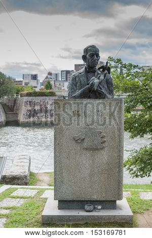 Hiroshima Japan - September 20 2016: One half of the Literature Monument in honor of the Japanese writer Miekichi Suzuki. His bust and him holding peace pigeons at Peace Memorial Park.