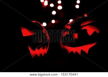 Two Halloween Pumpkins With Red Bokeh Light On Black Background