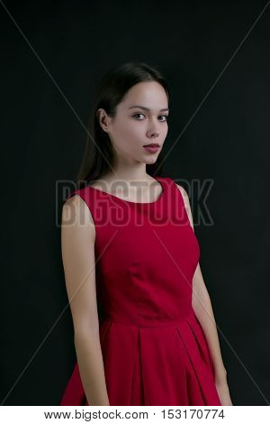 beautiful girl in a red dress on a black background.