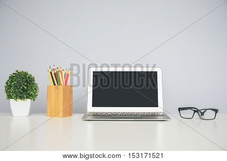 Front view of creative workplace with blank notebook glasses colorful pencils in wooden box and decorative plant. Mock up