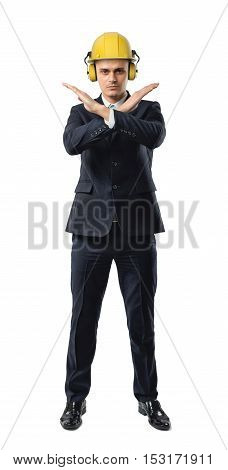 A businessman full height wearing a yellow helmet with earphones, giving a forbidding or stopping sign with his crossed arms isolated on a white background. Business and management. Building and construction. Giving orders.