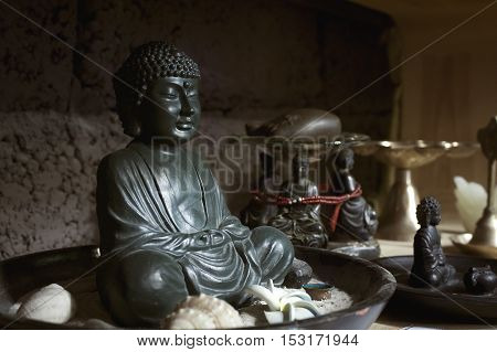 A statue of Buddha sitting peacefully in a cup with sand and shells, surrounded by smaller statues.