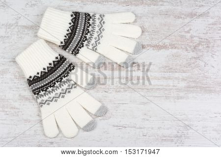 A pair of winter knitted gloves on white wooden background
