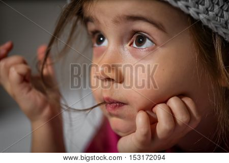 portrait of a little beautiful girl in a knitted hat closeup