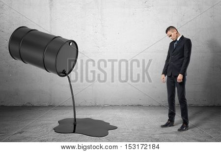 An inclined barrel with black liquid pouring out of it on a grey floor and a dissapointed sad businessman full height, on the grey background. Business and finance. Oil and gas industry. Failures and problems.