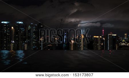 Night illuminated Kuala Lumpur, Malaysia. View from rooftop swimming pool. Rippling water in foreground