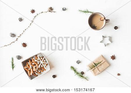 Christmas composition. Cup of coffee gift larch branches cinnamon sticks anise star christmas cookies. Flat lay top view