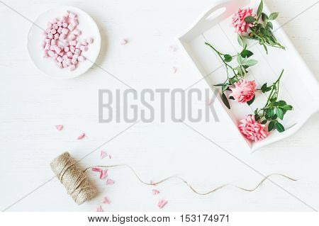 Workspace. Rose flowers. Flat lay top view