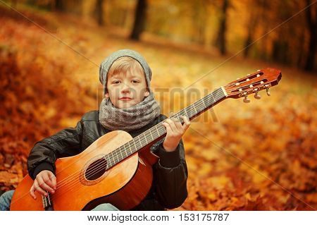 Little boy playing guitar on nature background autumn day. Children's interest in music
