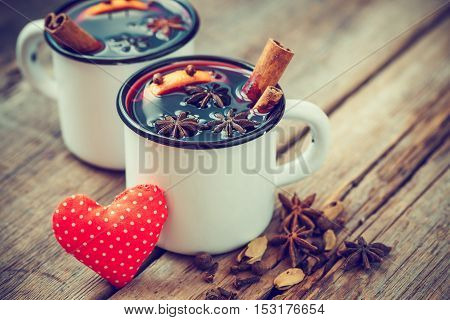 Mulled Wine In Mugs, Red Heart And Spice On Old Wooden Table.