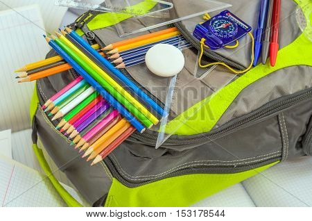 School backpack with bright colored pencils rulers and school supplies