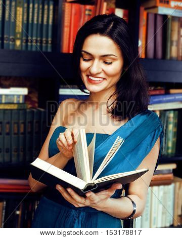 portrait of beauty young brunette woman reading book in library smiling, muslim girl in education, lifestyle people concept close up