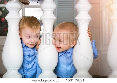 Two cute boy kid playing on porch decorated in Christmas style. Waiting for New year in festive interior