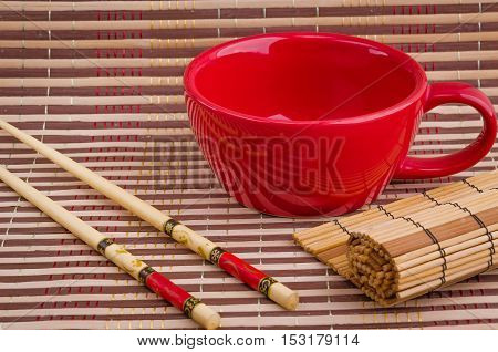empty cup and sushi chopsticks on a bamboo napkin