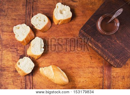 Sweet snack with fresh baguette and chocolate on a wooden table