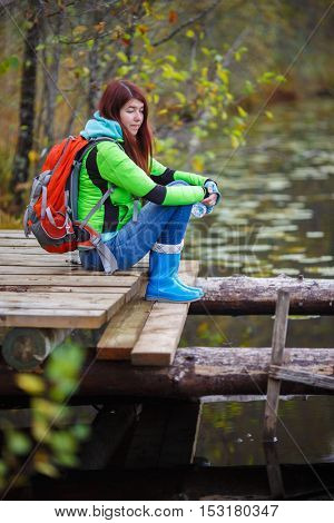 Young brunette with travel backpack sits on bridge by pond