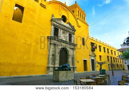 CARTAGENA COLOMBIA - MAY 25: Statue by Fernando Botero in Santo Domingo plaza by a yellow church in Cartagena Colombia on May 25 2016