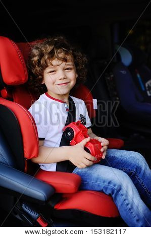 baby boy with curly hair sitting in red car seat in the cabin minibus
