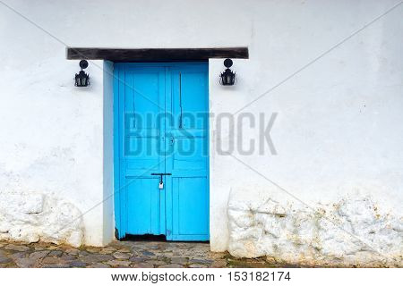 View of old wooden door on white colonial building in Villa de Leyva Colombia