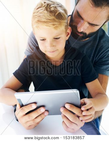 Father and his little son playing together on mobile computer, resting indoor.Bearded man with young boy using tablet PC in sunny house.Vertical, blurred background