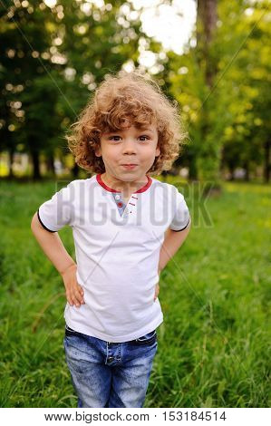 baby boy with curly red hair grimaces on a green background