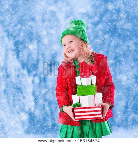 Little girl in red and green knitted hat holding Christmas present boxes in winter park on Xmas eve. Kids play outdoor in snowy winter forest. Children opening presents. Toddler kid playing with gifts