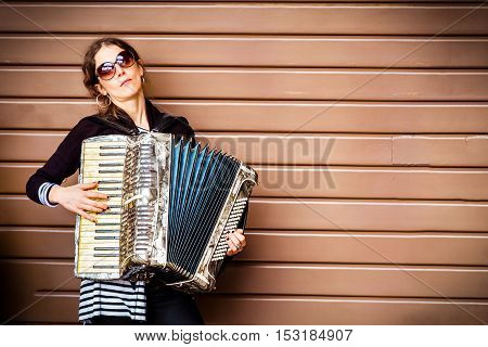 Bologna October 22 2016: A woman play accordion leaning on a brown closed shop shutter