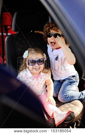 children sit in the car and play. little boy and girl in sunglasses laugh in the car