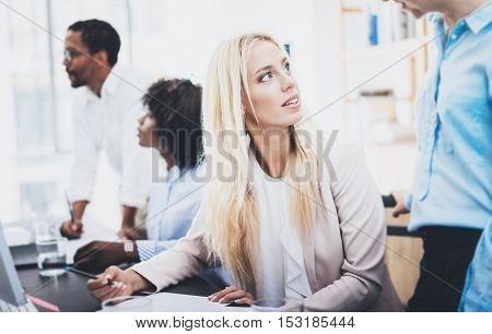 Group of four coworkers discussing business project in office. Beautiful woman talking with colleague. Horizontal, blurred background
