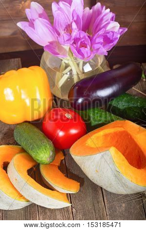 Pumpkin and vegetables - a cucumber and tomato. Three grades of pumpkin with an orange and gray peel one of them is cut by pieces on a wooden table.