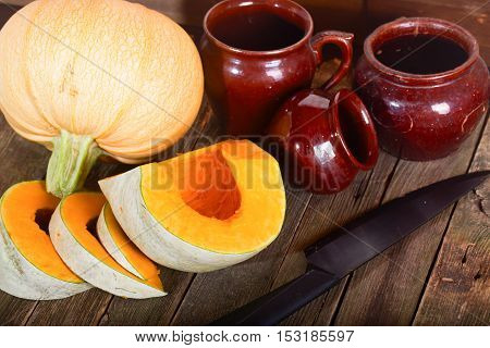 Pumpkin and ceramic pots on a wooden table. Three grades of pumpkin with an orange and gray peel one of them is cut by pieces rural style.