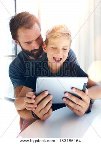 Young boy sitting with father at the table and using pc tablet in modern loft. Vertical, blurred background. Sunlights effect