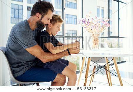 Young boy sitting with father at the table and playing together pc tablet in modern loft. Horizontal, blurred background