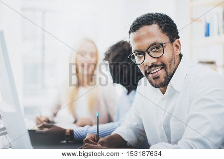 Dark skinned entrepreneur wearing glasses, working in modern office.African american man in white shirt looking and smiling at the camera.Horizontal, blurred background.