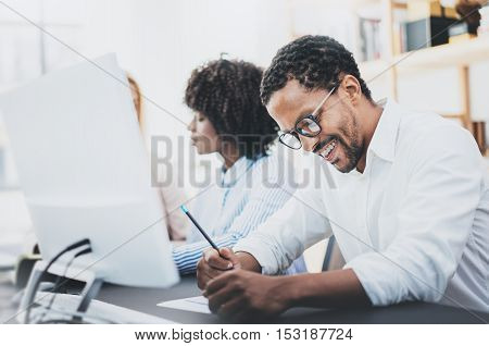 Three young coworkers working together in a modern office.African american man in white shirt smiling in workplace. Horizontal, blurred background.