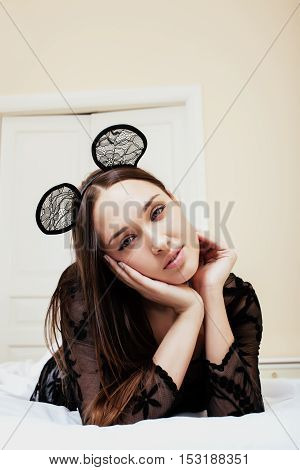 young pretty brunette woman wearing sexy lace mouse ears, laying waiting dreaming in bed close up