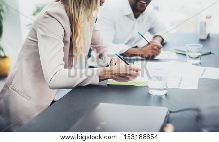 Closeup of two young coworkers working together on modern business project.Horizontal, blurred background.