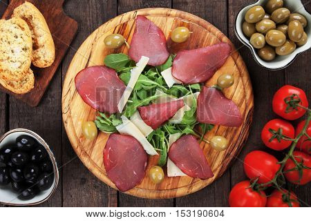 Italian bresaola, slices of cured beef served with grana padano cheese and rocket salad