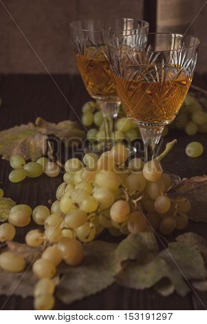 Two crystal glasses with white wine, grapes and dry leaves