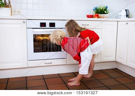 Little boy and girl brother and sister baking delicious apple pie in white kitchen. Kids looking at fruit cake in the oven. Children bake at home. Toddler child and preschooler waiting for pastry.