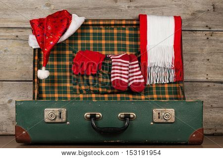 Open suitcase with a Christmas clothes on a wooden background old surface.