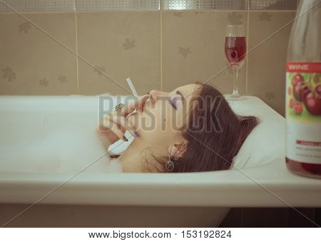 Naked girl smoking and drinking wine in bubble bath