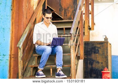 Young man typing on notebook sitting on rusty steps outside - Handsome guy looking down using pc outdoor on suburb old industrial site background - Nostalgic vintage filter look