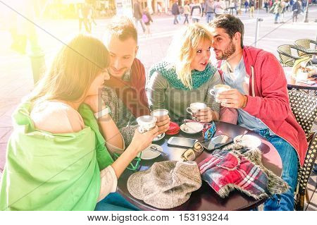 Group of best friends drinking cappuccino at bar cafe restaurant - Teenagers talking and sharing happy moments together around table - Concept of friendship and relations - Sun halo filter