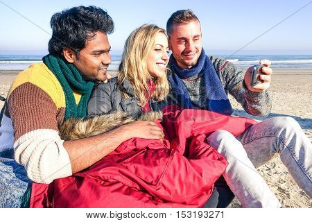 Multiracial young friends taking selfie on the beach in sunny winter day - Multiethnic teenagers having fun looking mobile phone - Concept of friendship happy moment with colorful vintage filter tones